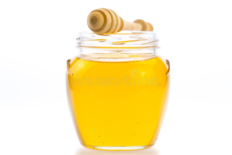 Glass krus av ny honung med drizzler arkivfoton