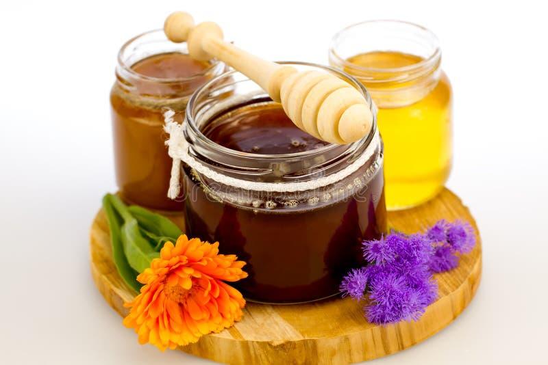 glass krus av ny honung med drizzler och blommor arkivbild