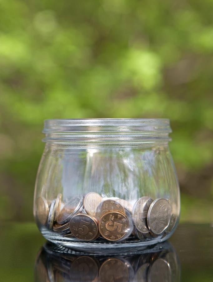 Glass krus med mynt på grön bakgrund royaltyfria bilder