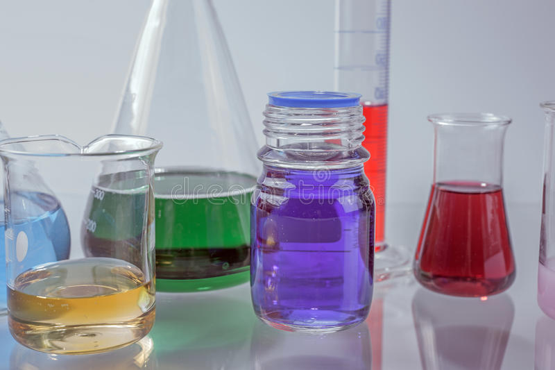 Glass laboratory apparatus with color water. On the table stock image