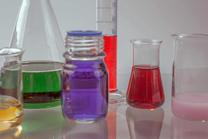 Glass laboratory apparatus with color water. On the table royalty free stock photography