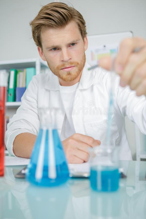Glass laboratory chemical test tubes with blue liquidman wear royalty free stock photo