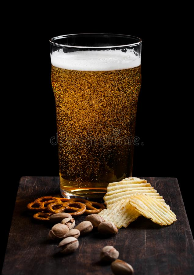 Glass of lager beer with snack on vintage wooden board on black background. Pistachios and pretzel with potato crisps. royalty free stock photography