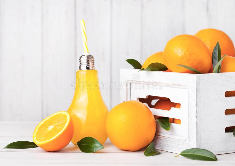 Glass lamp shape of organic fresh orange juice. With raw oranges in white wooden box stock photography