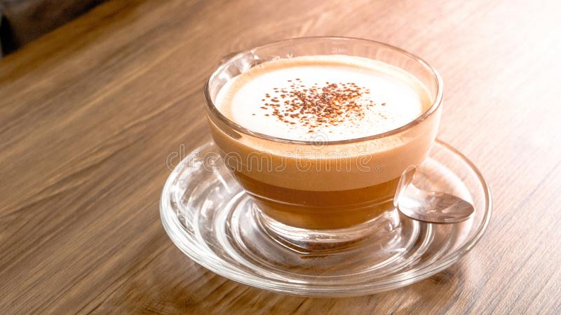 Glass latte coffee cup on wooden table with spoon and copy space stock image
