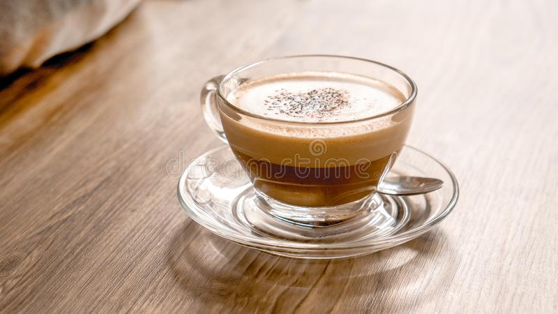 Glass latte coffee cup on wooden table with spoon and copy space royalty free stock photos