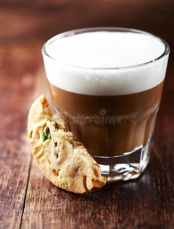 Glass of latte coffee and pistachio cookie on wooden background royalty free stock photo