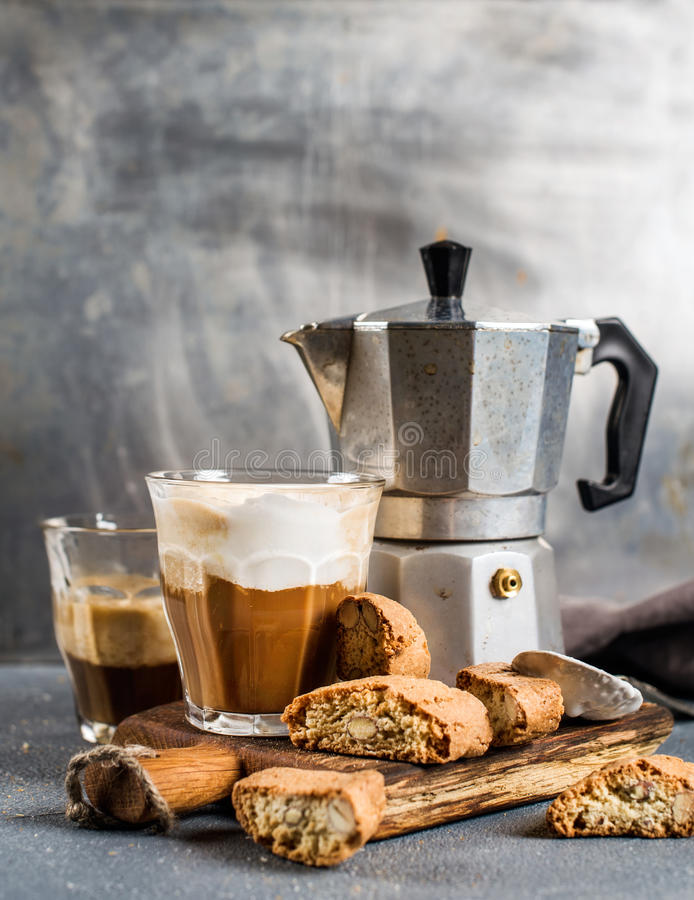 Glass of latte coffee on rustic wooden board, cantucci biscuits and steel Italian Moka pot, grey background. Selective focus royalty free stock photos