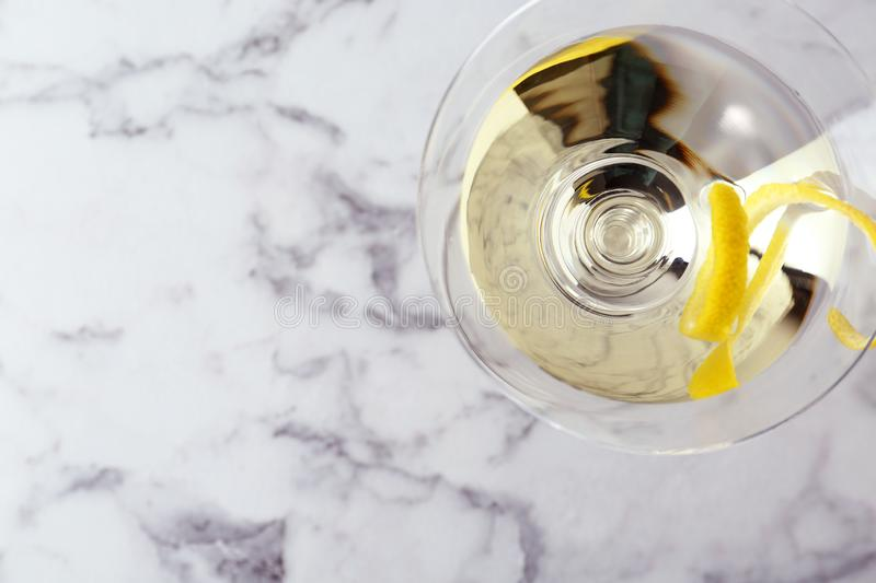 Glass of lemon drop martini cocktail with zest on white marble table. Space for text. Glass of lemon drop martini cocktail with zest on white marble table, top royalty free stock photos