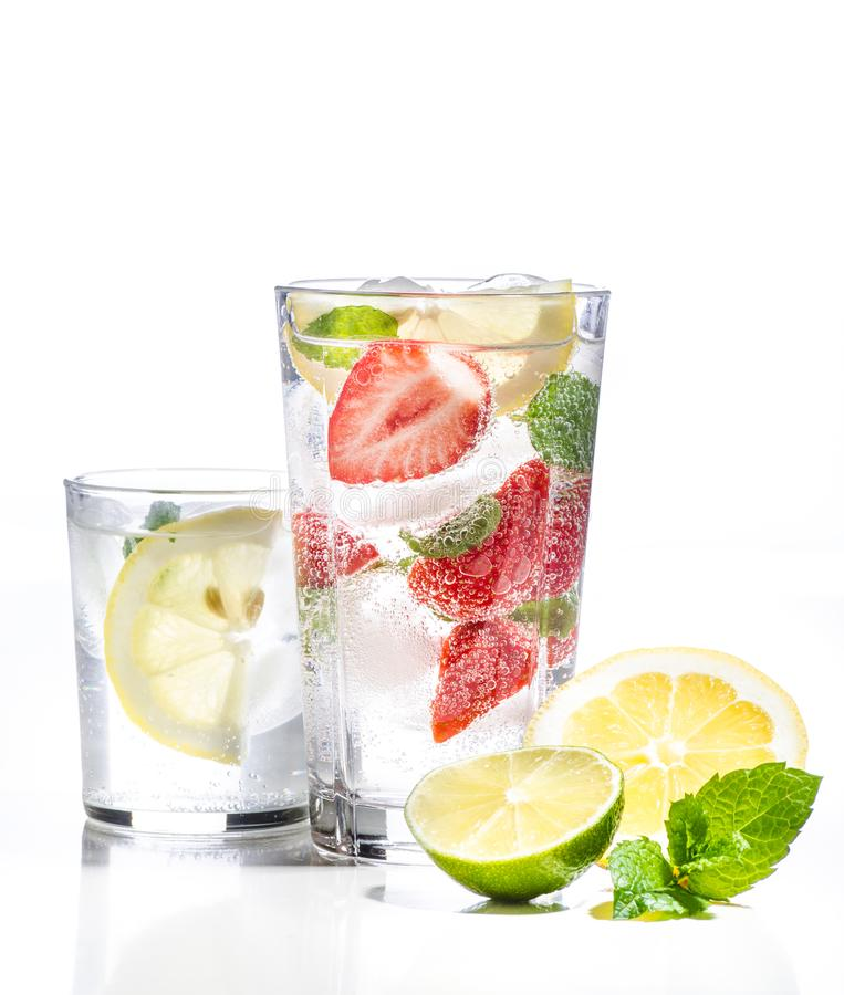 Glass of lemonade with lemon, lime and strawberries on white background stock image