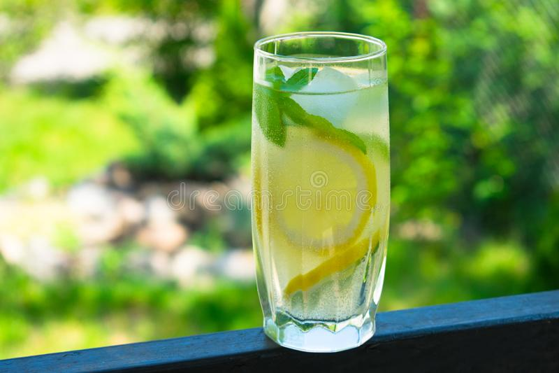 A glass of lemonade with mint on the background of fresh summer green grass. Cooling drink. stock images