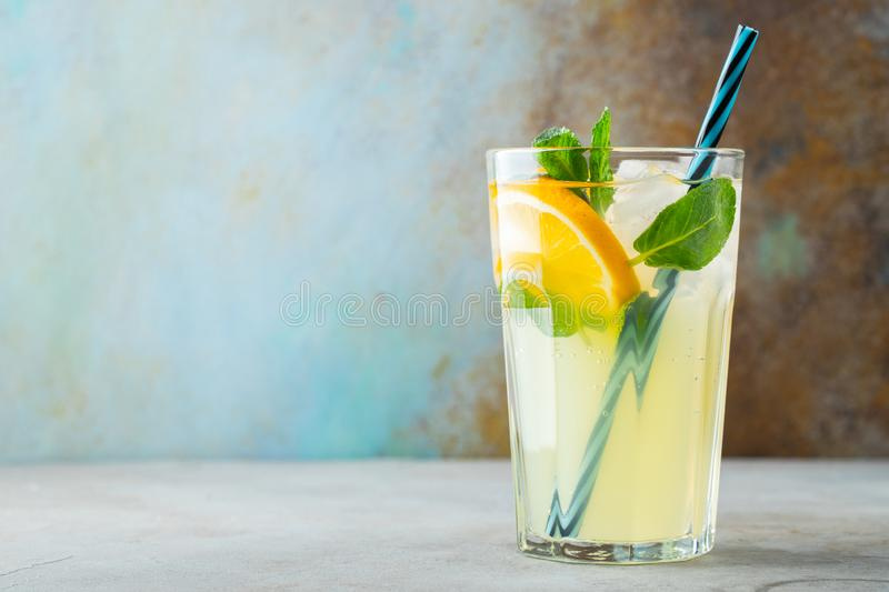 Glass with lemonade or mojito cocktail with lemon and mint, cold refreshing drink or beverage with ice on rustic blue background. royalty free stock photos