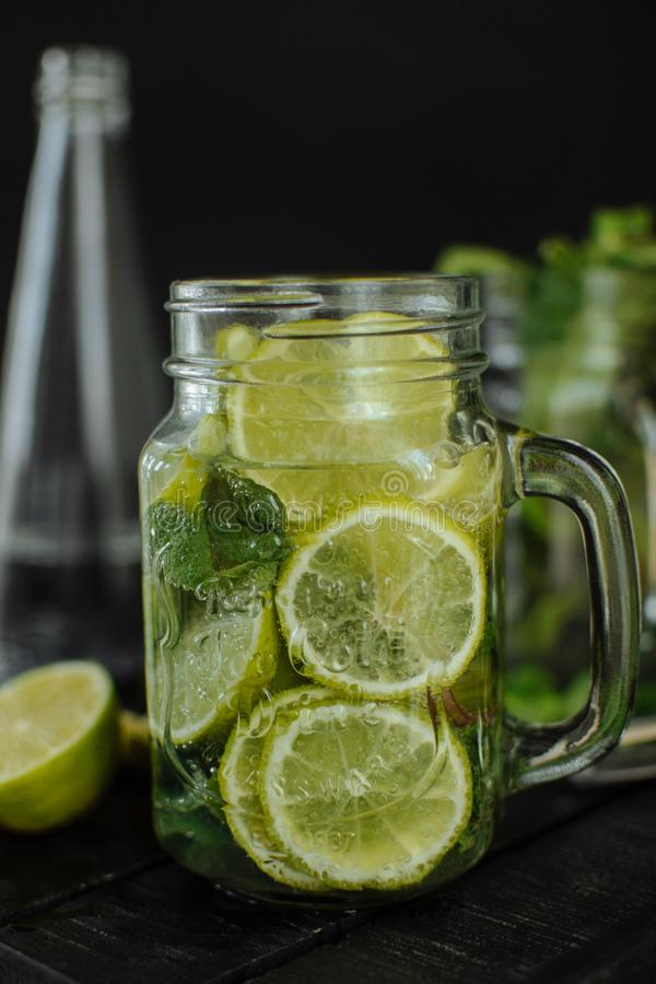 A glass of lemonade with sliced lime and lemon in a mug on a black background. stock image