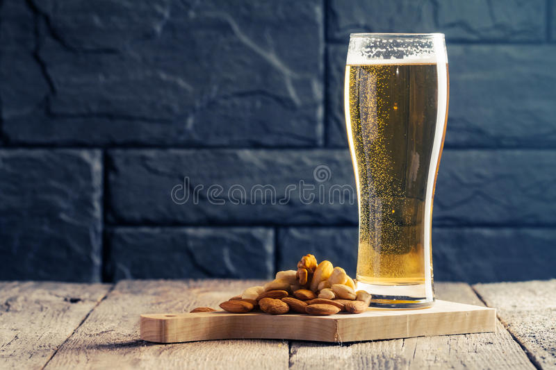 Glass of light beer. With bubbles near black wall stock photo
