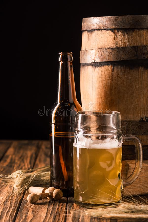 glass of light beer with foam beer bottle wheat and wooden barrel at table stock photography