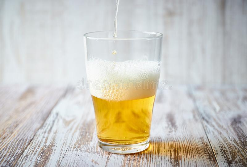 A glass of light beer with foam on a wooden background, close-up. vertical view of the glass. stock photo