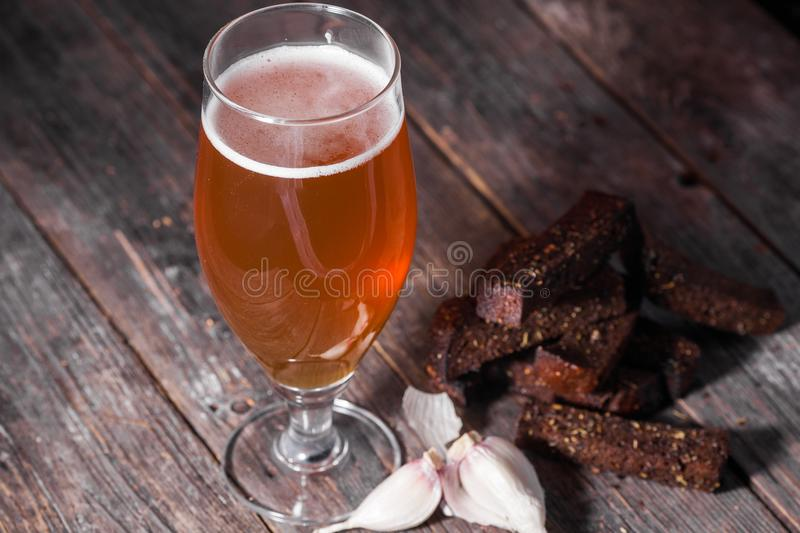 A glass of light beer and fried hot aromatic garlic toasts of bl. Ack bread on a table made of textured old wooden boards royalty free stock photography