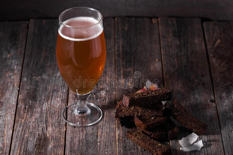 A glass of light beer and fried hot aromatic garlic toasts of bl. Ack bread on a table made of textured old wooden boards royalty free stock image