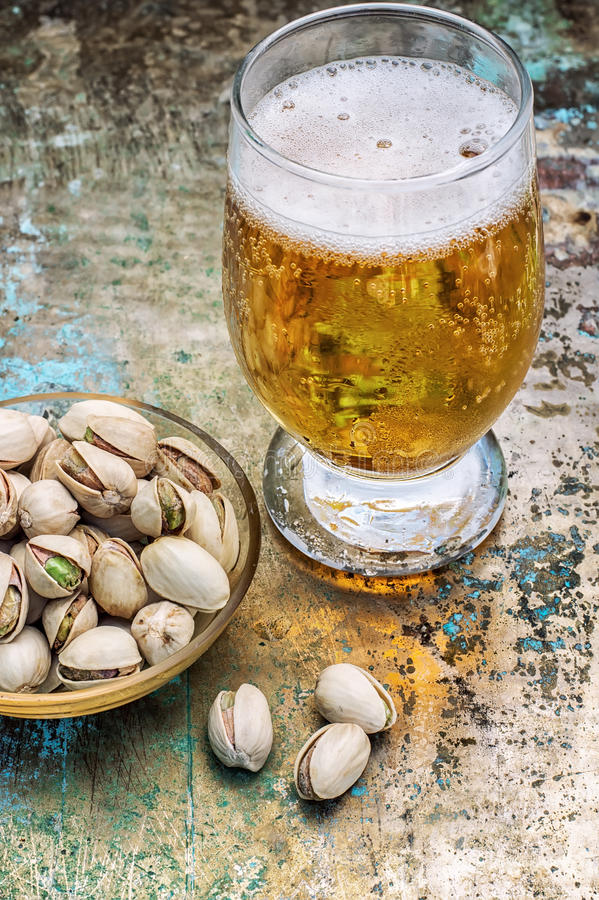 Glass of light beer. One glass glass of light beer with scattered on the table pistachios.Photo tinted stock images