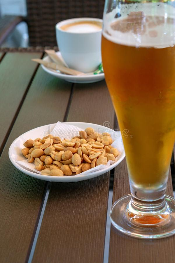 Glass with light beer, roasted peanuts and a cup of americano on a wooden table. Soft focus stock images