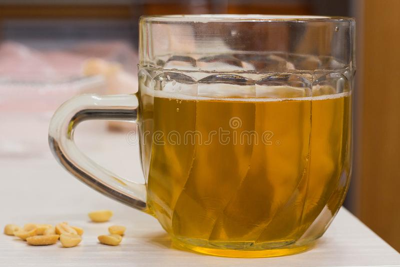 Glass of light beer, salted peanuts. Home furnishings table ale pub malt pitcher alcohol bar barley beaker beverage booze brewed brewery brown bubble stock photography
