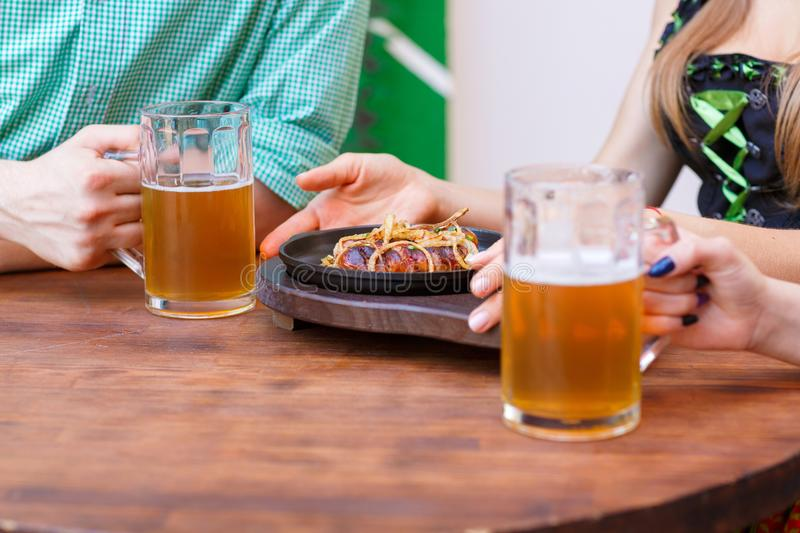 Glass of light beer with a sausage plate on a dark table in the pub. royalty free stock image