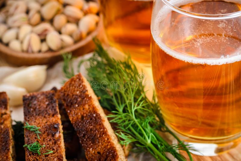 A glass of light beer and snacks, rye rusks with dill on a wooden table. A glass of light beer and snacks, pistachios, rye rusks with dill on a wooden table royalty free stock images