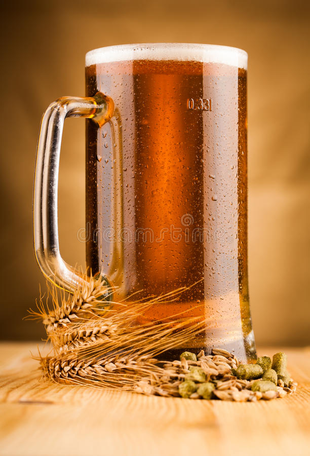 Glass of light beer on table. Glass of light beer on wooden table royalty free stock photography