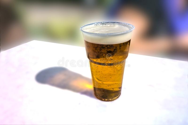 A glass of light beer on a white table stock photo