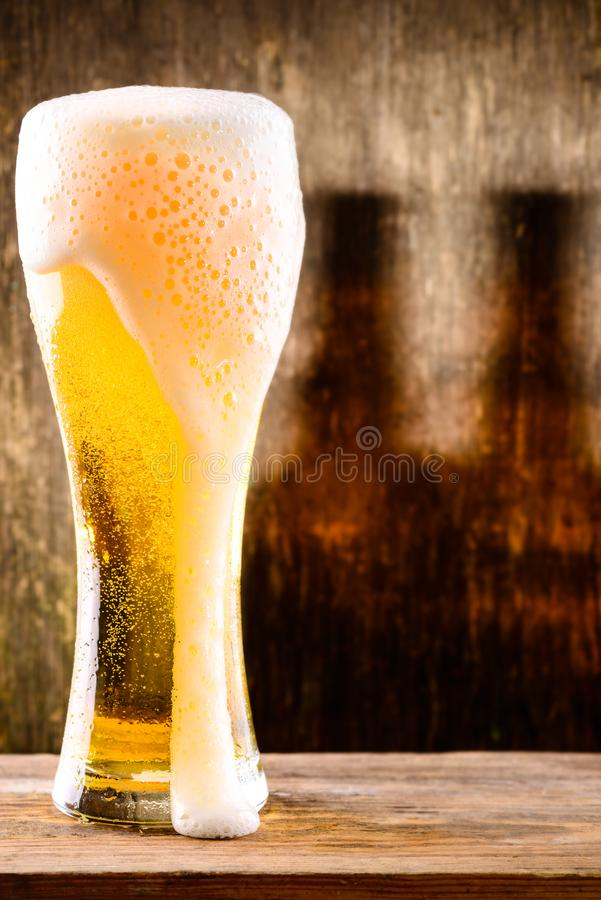 Glass of light beer on a wooden background with shadow of two bo stock photography