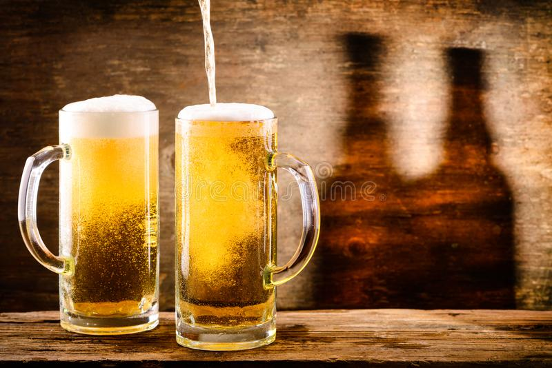 Glass of light beer on a wooden background with shadow of two bo stock image
