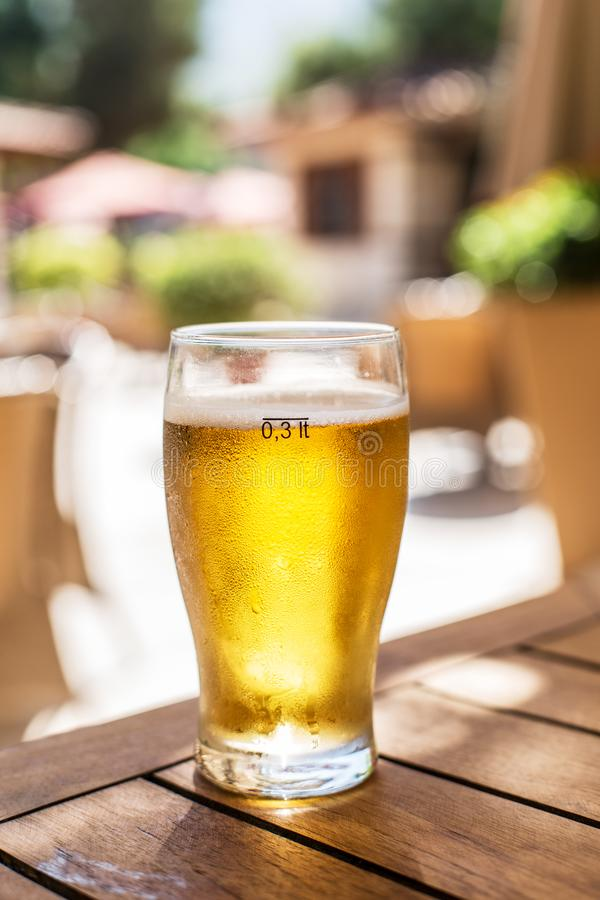 Glass of light beer on the wooden table. royalty free stock photos