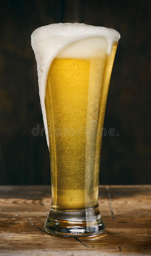 Glass of light beer on a wooden table royalty free stock images