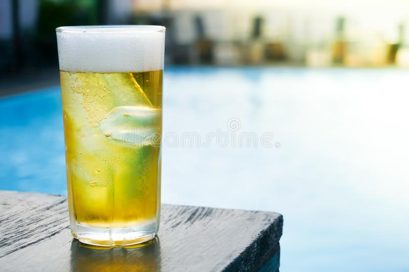 Glass of the light beer on the wooden table at pool. Glass of the light beer on the wooden table at the pool royalty free stock photography