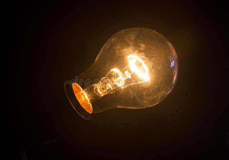 Glass light bulb with burning filament on black background. Glass light bulb on black stock image