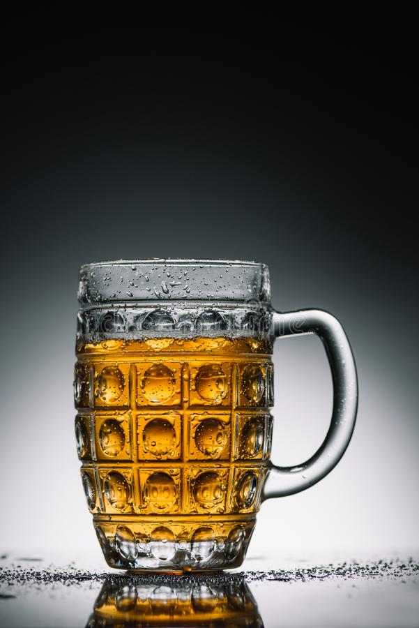 Glass with light cold beer with bubbles on gray. Reflecting surface stock photography
