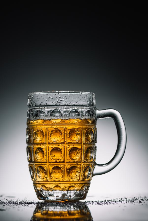 Glass with light cold beer with bubbles on gray reflecting surface royalty free stock image