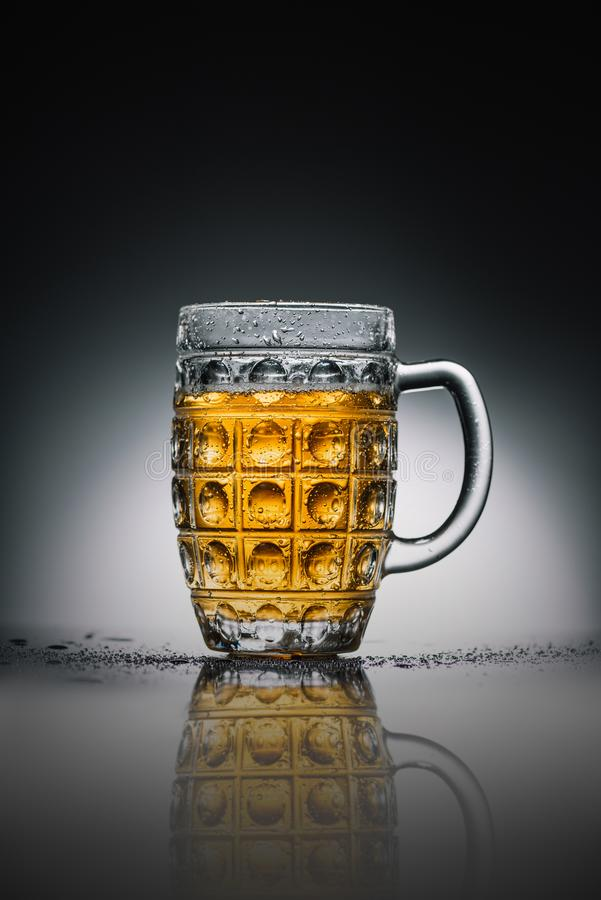 Glass with light cold beer on gray. Reflecting surface royalty free stock photography