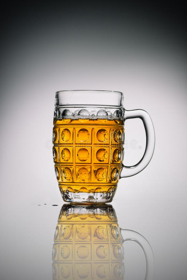 Glass with light cold beer in transparent glass on gray. Reflecting surface royalty free stock images