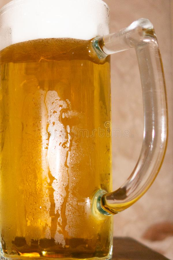 Glass of light cold frothy beer, nuts on an old wooden table. stock photos