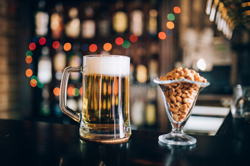 Glass of light cold frothy beer, nuts in pub. Drinks royalty free stock photo