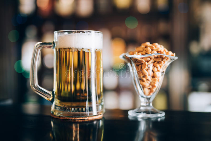 Glass of light cold frothy beer, nuts in pub stock photo