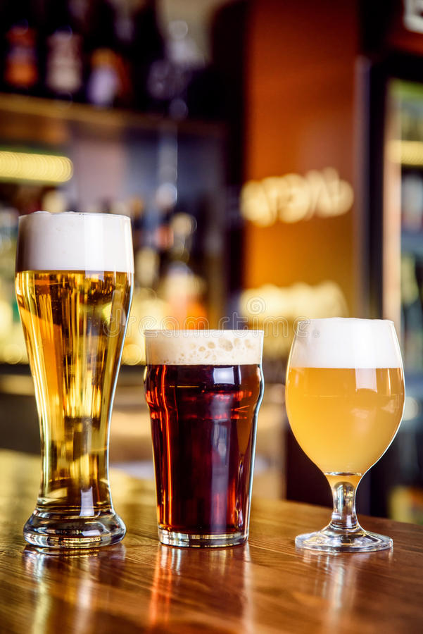 Glass of light and dark beer on a pub with bokeh background royalty free stock image