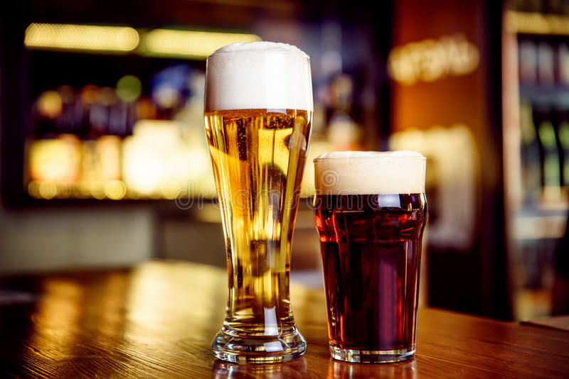 Glass of light and dark beer on a pub with bokeh background stock images