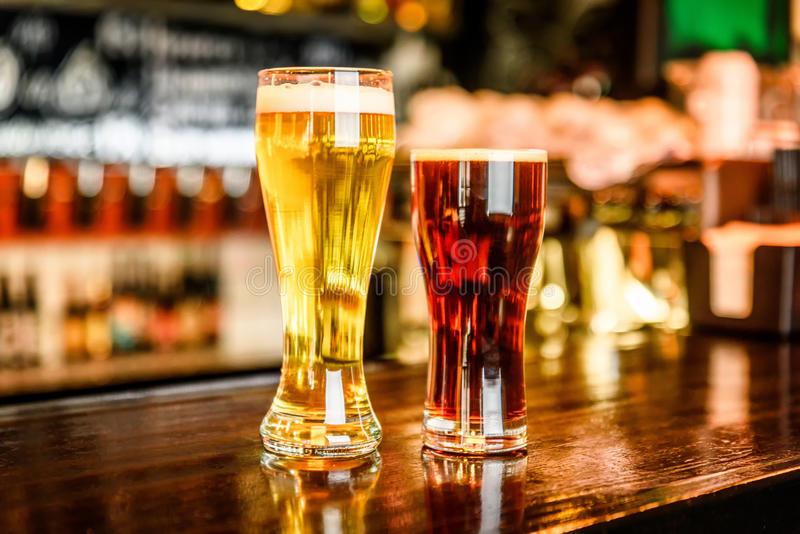 Glass of light and dark beer on a pub with bokeh background royalty free stock images