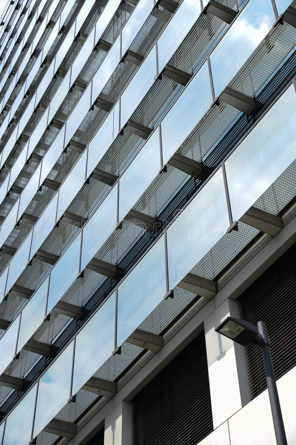 Glass light. Modern architecture building reflecting the sky, windows with glass Railing elements, horizontal and vertical structure / pattern with street light royalty free stock image