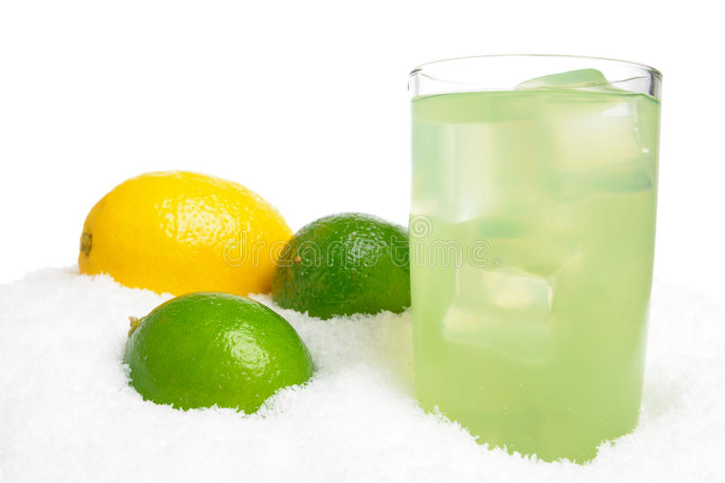 Glass of lime juice with ice cubes,limes,lemon on snow on white. Background royalty free stock photography