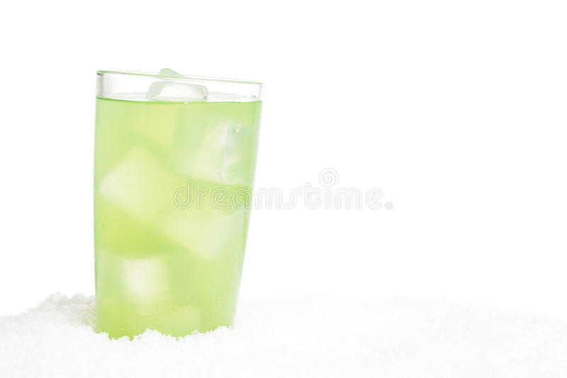 Glass of lime juice with ice cubes on snow on white. Background royalty free stock images