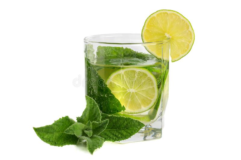 A glass with a lime and mint drink on an isolate against a white background royalty free stock photography