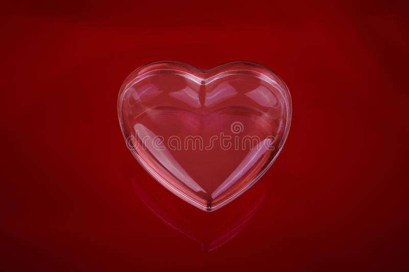 Glass love heart. On red background stock images